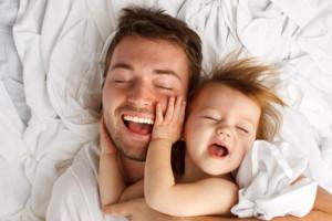 Vater und Tochter lachen im Bett